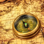 18731117-Vintage-still-life-Vintage-compass-lies-on-an-ancient-world-map--Stock-Photo